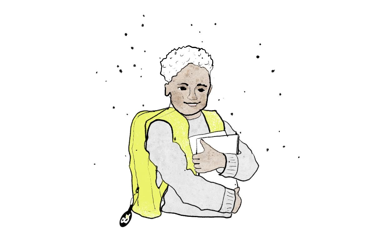 Ein Junge mit Schulranzen hält Schulbücher im Arm