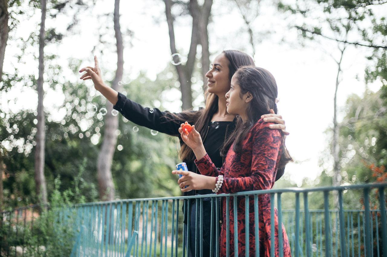Patin und Patenschülerin im Park mit Seifenblasen