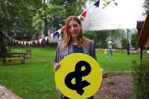 Junge Frau steht mit dem Schülerpaten-& vor einer grünen Wiese in einem Hinterhof